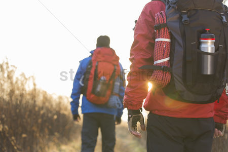 Rope : Rear view of male backpackers walking in field