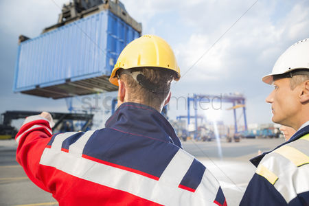 Supervisor : Rear view of male workers discussing in shipping yard