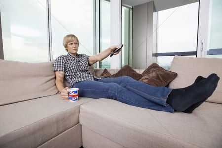 British ethnicity : Relaxed mid-adult man watching television while having coffee on sofa at home