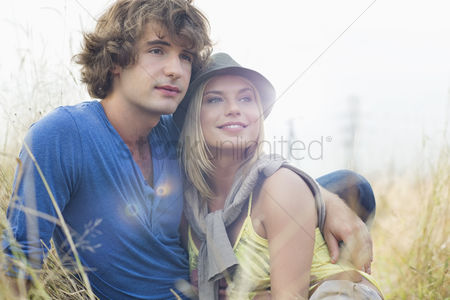 Girlfriend : Romantic young couple looking away while sitting in field