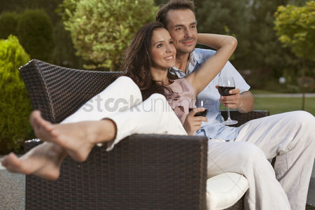 Girlfriend : Romantic young couple on easy chair looking away in park