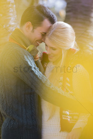 Shyness : Romantic young couple smiling in park during autumn