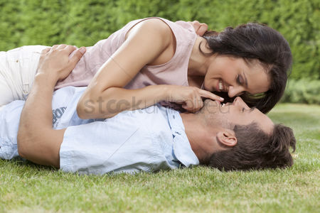Girlfriend : Romantic young woman touching man s lips while lying on him in park