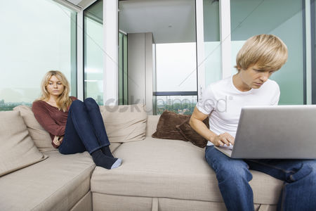 Worry : Sad woman beside man using laptop in living room at home