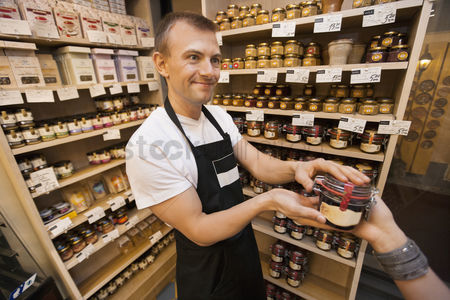 Supermarket : Salesman giving jar of jam to female customer in grocery store