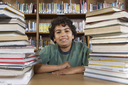 Pupil : School boy sitting at desk with books in library portrait