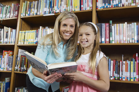Pupil : School girl and teacher holding book in library portrait