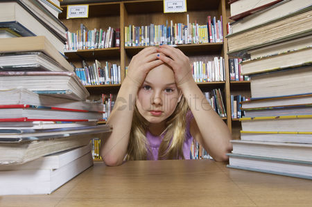 School : School girl sitting at desk with books in library portrait