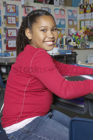Pupil : School girl sitting in classroom portrait