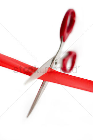 Celebrating : Scissors cutting through a red ribbon