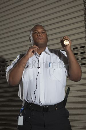 Earpiece : Security guard patrols with torch