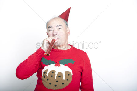 Excited : Senior adult man wearing christmas jumper blowing party blower