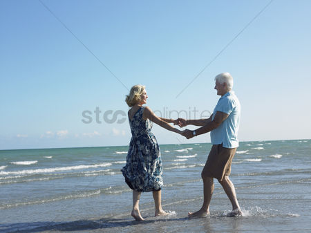 Two people : Senior couple holding hands on beach while dancing side view