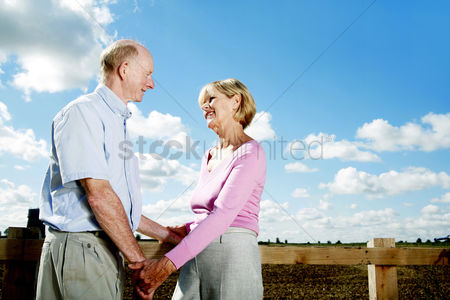 Aging process : Senior couple holding hands while looking at each other