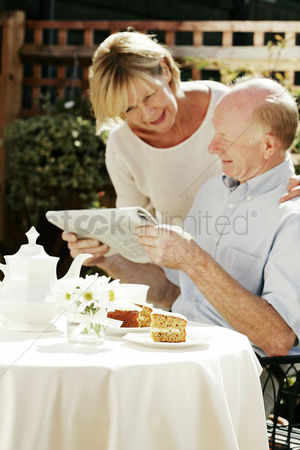 Husband : Senior couple reading newspaper while having breakfast