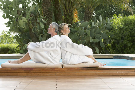 Closeness : Senior couple relaxing by poolside