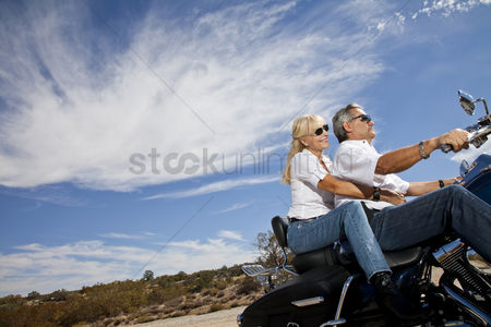 On the road : Senior couple riding motorcycle on desert road