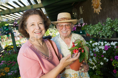 Choosing : Senior couple shopping for flowers at plant nursery portrait