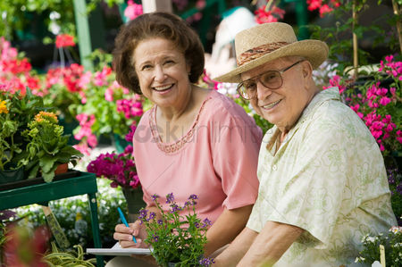 Two people : Senior couple sitting among flowers at plant nursery portrait