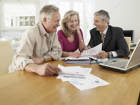 Smile : Senior couple sitting at table with financial advisor