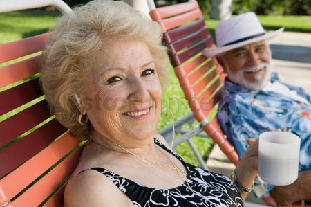 Posed : Senior couple sitting on lawn chairs woman listening to earphones and holding cup portrait