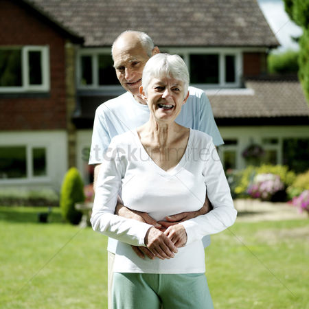 Two people : Senior couple standing outside their house