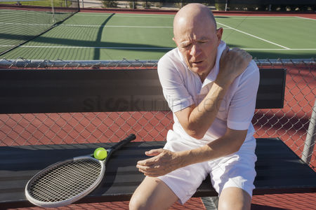 Three quarter length : Senior male tennis player with shoulder pain sitting on bench at court