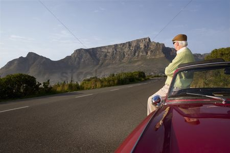 Vintage car : Senior man admires view leaning on vintage racing car on signal hill  cape town  south africa