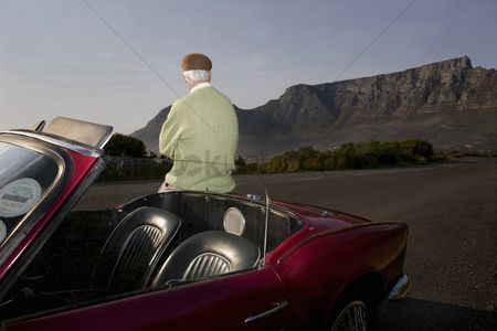 On the road : Senior man admires view leaning on vintage racing car on signal hill  cape town  south africa