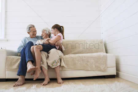 Ponytail : Senior man and woman sitting with granddaughter on woman s knee on couch