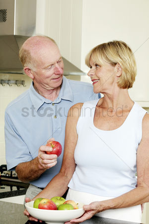 Aging process : Senior man getting an apple from his wife