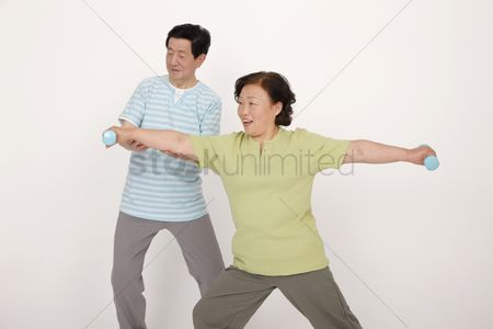 Dumbbell : Senior man guiding senior woman in lifting weights
