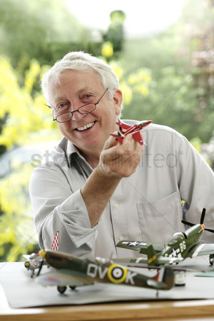 Sets : Senior man holding model airplane