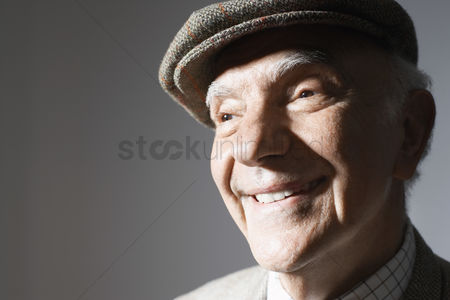 Background : Senior man in flat cap close up in studio