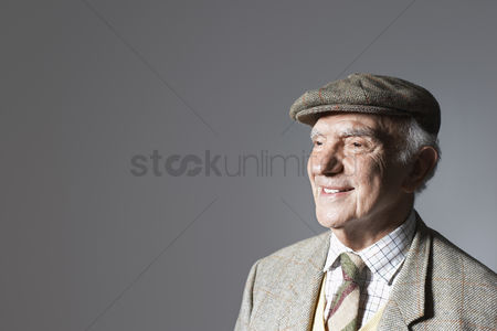 Jacket : Senior man in flat cap head and shoulders in studio
