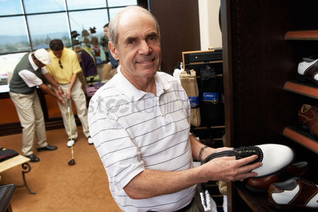 Shopping background : Senior man in golf shop shopping for golf shoes