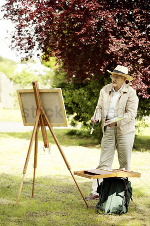Bespectacled : Senior man painting in the park