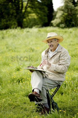 Paint brush : Senior man sitting on a chair drawing