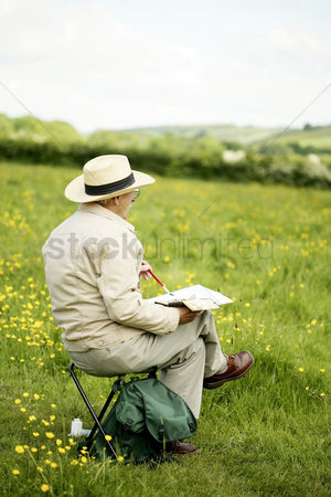 Paint brush : Senior man sitting on the chair drawing