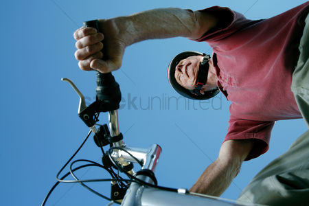 Enjoying : Senior man with helmet riding on bicycle