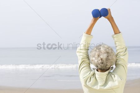 Fitness : Senior woman excercising with dumbbells on beach