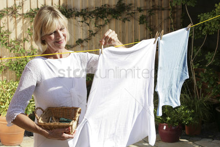 Retirement : Senior woman hanging clothes on the clothesline