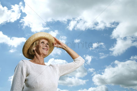 Retirement : Senior woman holding her hat while looking up