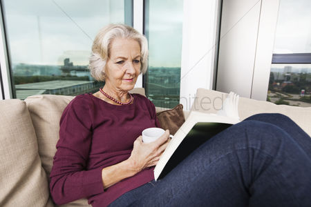 Senior women : Senior woman reading book on sofa at home