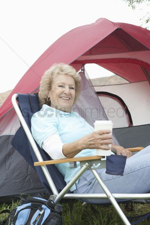 Pitch : Senior woman sits relaxing outside a tent