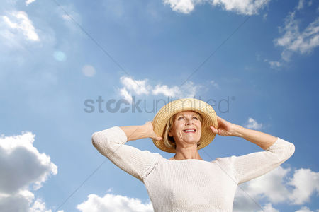 Outdoor : Senior woman smiling while holding her hat