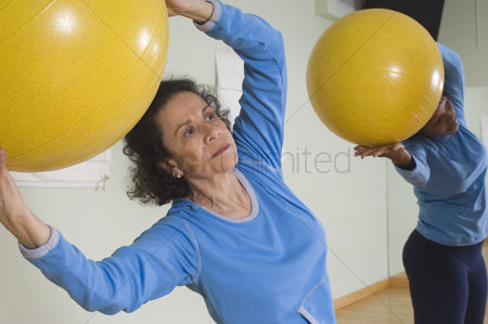 Fitness : Senior woman using exercise ball in fitness class