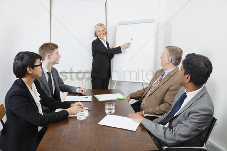 Leadership : Senior woman using whiteboard in business meeting