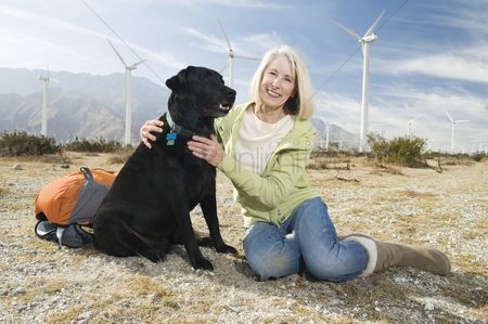 Senior women : Senior woman with dog near wind farm