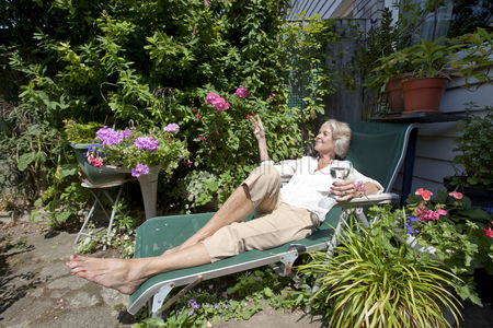 Retirement : Senior woman with wineglass relaxing on lounge chair in garden